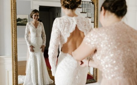 a girl wearing a wedding and standing in front of mirror another girl helping